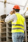 Rear view image of male architec in safety vest and hardhat talking by phone. Rear view photo of male architec in safety vest and hardhat talking by phone Stock Images