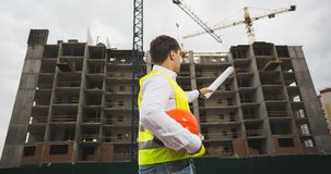 Rear view image of male architect in green safety vest showing building site. Rear view photo of male architect in green safety vest showing building site Stock Image