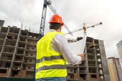 Rear view image of male architect in hardhat and vest looking at working building cranes. Rear view photo of male architect in hardhat and vest looking at Stock Photos