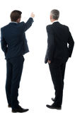 Rear-view image of two businessmen. Businessman showing something to his partner Stock Images