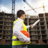 Rear view image of young engineer pointing at building with blue Stock Image