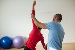 Rear view of instructor assisting student in exercising at health club. Rear view of male instructor assisting student in exercising at health club Royalty Free Stock Images
