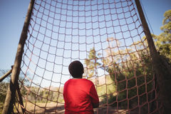 Rear view of kid looking at net during obstacle course stock photo