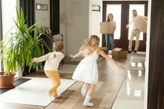 Rear view at kids running to parents on moving day. Rear view at kids running to parents holding boxes on moving day or after shopping, excited happy children stock images