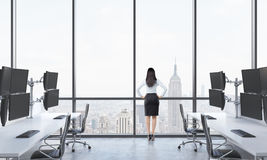 Rear view of a lady in formal suit who is looking out the window in the modern panoramic office with New York view. White tables e Royalty Free Stock Photos