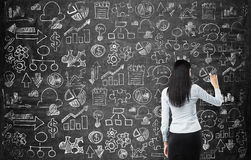 Rear view of the lady who is drawing business icons on the chalkboard as a wall. Royalty Free Stock Photos