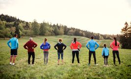 Rear view of large group of multi generation sport people standing in nature. stock photo
