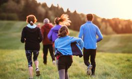 Rear view of large group of people cross country running in nature. A rear view of large group of people cross country running in nature at sunset royalty free stock images