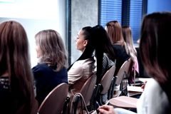 Rear view.the listeners sitting in the conference room. stock photography