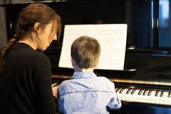 Rear view of a little boy learning piano from Royalty Free Stock Photo