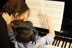 Rear view of a little boy learning piano from Royalty Free Stock Photos