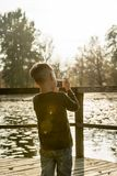Little boy photographing nature with a compact camera outdoors a. Rear view of a little boy photographing nature with a compact camera outdoors at the lake Stock Photography