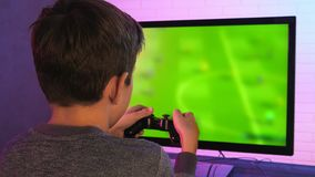 Rear view of a little boy playing MMORPG video game at his computer stock footage