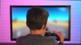 Rear view of a little boy playing racing game. Stock footage stock video footage