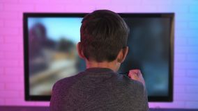 Rear view of a little boy playing shooter video game at his computer stock footage