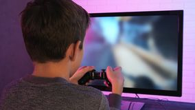 Rear view of a little boy playing shooter video game at his computer stock video footage