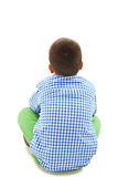 Rear view of little boy sitting on floor Stock Image