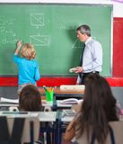 Rear View Of Little Boy Writing On Board In. Rear view of little boy writing on board while teacher looking at him in classroom Royalty Free Stock Photo