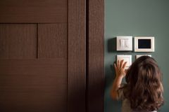 Rear view at little child girl playing turning light switches Stock Photo