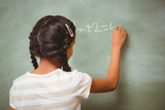 Rear view of little girl writing on blackboard. In the classroom Stock Photos