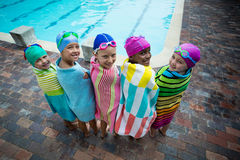 Rear view of little swimmers wrapped in towels at poolside Royalty Free Stock Photography