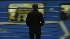Rear view of lonely young man shot from behind at subway station add look at watch waiting for the train. Businessman at. The station 4K stock video footage
