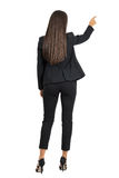 Rear view of long dark hair beauty pointing or presenting on her right side. Royalty Free Stock Images