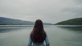 Rear view of long-hair brunette woman standing and enjoying scenic Alps and lake. 4k stock video footage