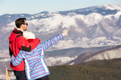 Rear view of a loving couple in fur hood jackets looking at snowed mountain range.  Royalty Free Stock Image
