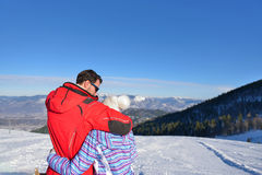 Rear view of a loving couple in fur hood jackets looking at snowed mountain range.  Stock Photography