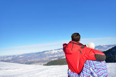 Rear view of a loving couple in fur hood jackets looking at snowed mountain range.  Stock Image
