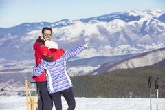 Rear view of a loving couple in fur hood jackets looking at snowed mountain range royalty free stock photo