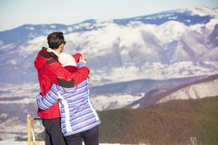 Rear view of a loving couple in fur hood jackets looking at snowed mountain range.  Royalty Free Stock Photography