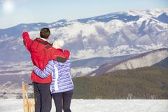 Rear view of a loving couple in fur hood jackets looking at snowed mountain range.  Stock Photos