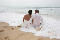 Rear view of loving couple relaxing on beach, kissing outdoors, Stock Photo
