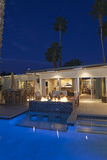 Rear view of luxury villa at night time with lit fire royalty free stock photography