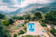 Rear view of luxury villa with swimming pool and sunbeds towards mountains and blue sky in Crete, Greece. stock photography