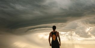 Fit man taking rest after workout against dramatic sky Stock Photo