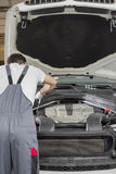 Rear view of male engineer repairing car in automobile repair shop stock photo