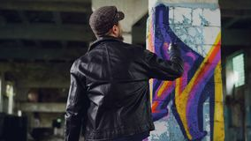Rear view of male graffiti artist in leather jacket painting on damaged column inside empty industrial building. Young. Rear view of male graffiti artist in stock footage