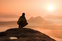 Rear view of male hiker sitting on the rocky peak  while enjoying a colorful daybreak above mounrains valley. Rear view of male hiker sitting on the rocky peak Stock Images