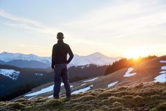 Male tourist enjoying beautiful panorama in the evening. Rear view of male hiker watching wonderful scenery in mountains during spring colorful sunset Royalty Free Stock Image