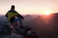 Rear view of male hiker in yellow black jacket sitting on rocky cliff while enjoying daybreak above valley. Rear view of male hiker in yellow black jacket Royalty Free Stock Images