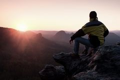 Rear view of male hiker in yellow black jacket sitting on rocky cliff while enjoying daybreak above valley. Rear view of male hiker in yellow black jacket Stock Photos