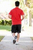 Rear View Of Male Runner Exercising On Suburban Street Stock Image