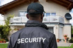 Rear View Of A Male Security Guard. In Front Of House stock photos