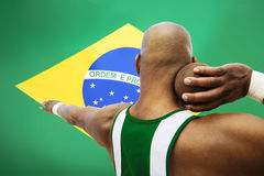 Rear view of male shot putter aiming against Brazilian flag Stock Photo