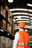 Rear View Of Male Supervisor At Warehouse. Rear view of male supervisor wearing protective vest and helmet at warehouse Royalty Free Stock Images