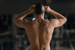 Rear view of a male swimmer adjusting his goggles. Rear view of a male swimmer adjusting his swimming goggles Stock Photography