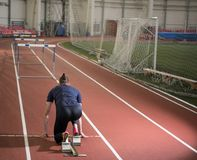 Rear view of an male track and field athlete preparing hurdling. Start positon from the blocks royalty free stock photo